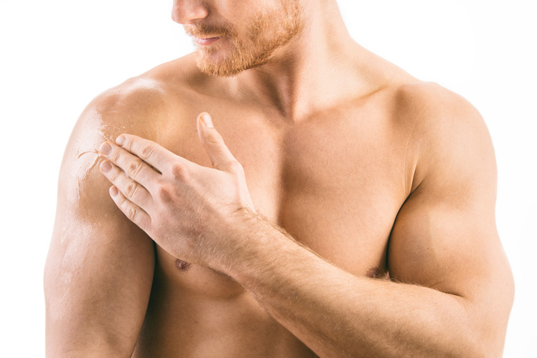 man applying male contraceptive gel to shoulder