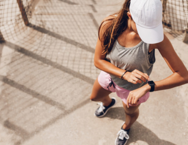 Woman running, using watch to exercise, fitness