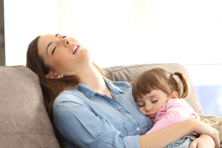 mum asleep on sofa with daughter in arms