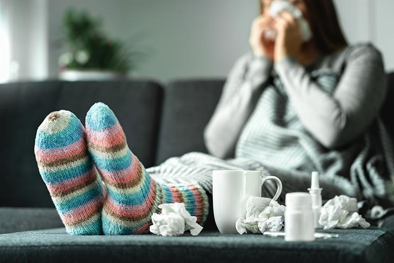 woman on sofa with tissues