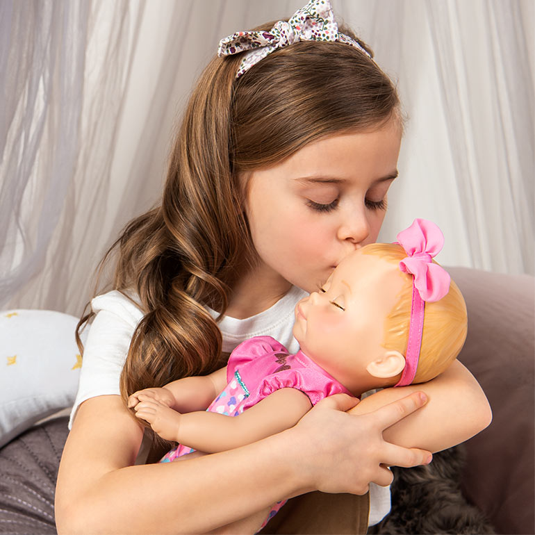 Little girl playing with Luvabella Newborn