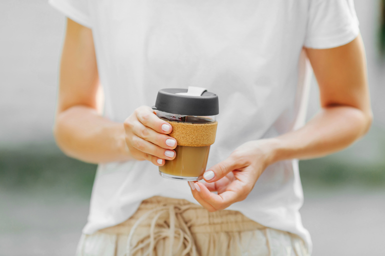 woman holding coffee in keep cup