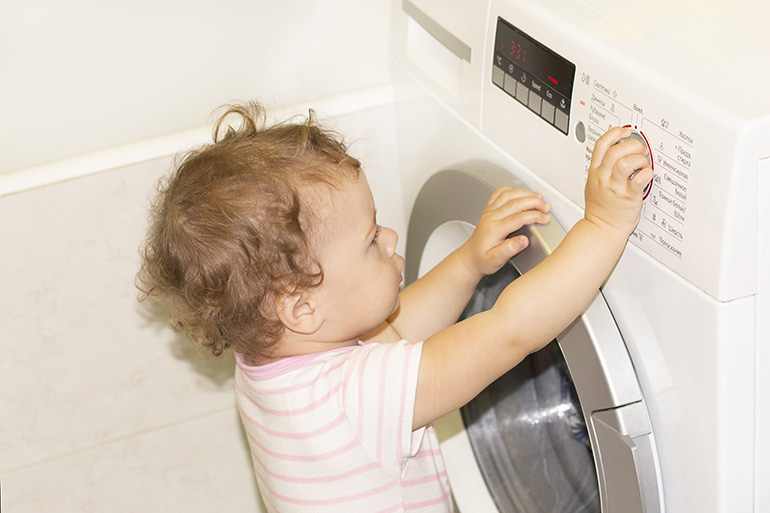 child playing in front load washing machine