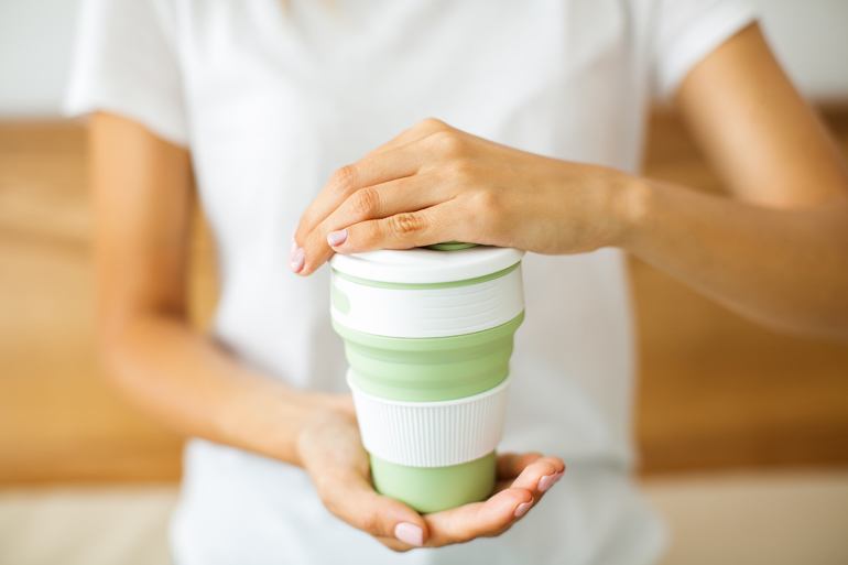 woman with coffee in reusable coffee cup