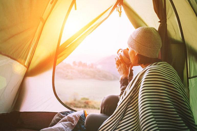 Woman drinking coffee in tent, camping - coffee moment