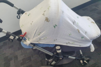 pram covered in muslin wrap
